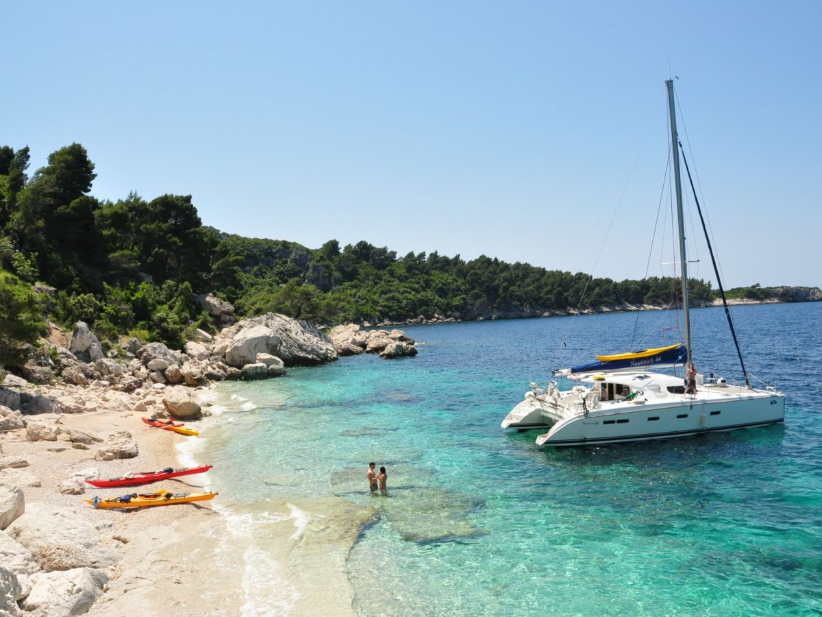 Sailing catamaran docked at an island and two people in the sea