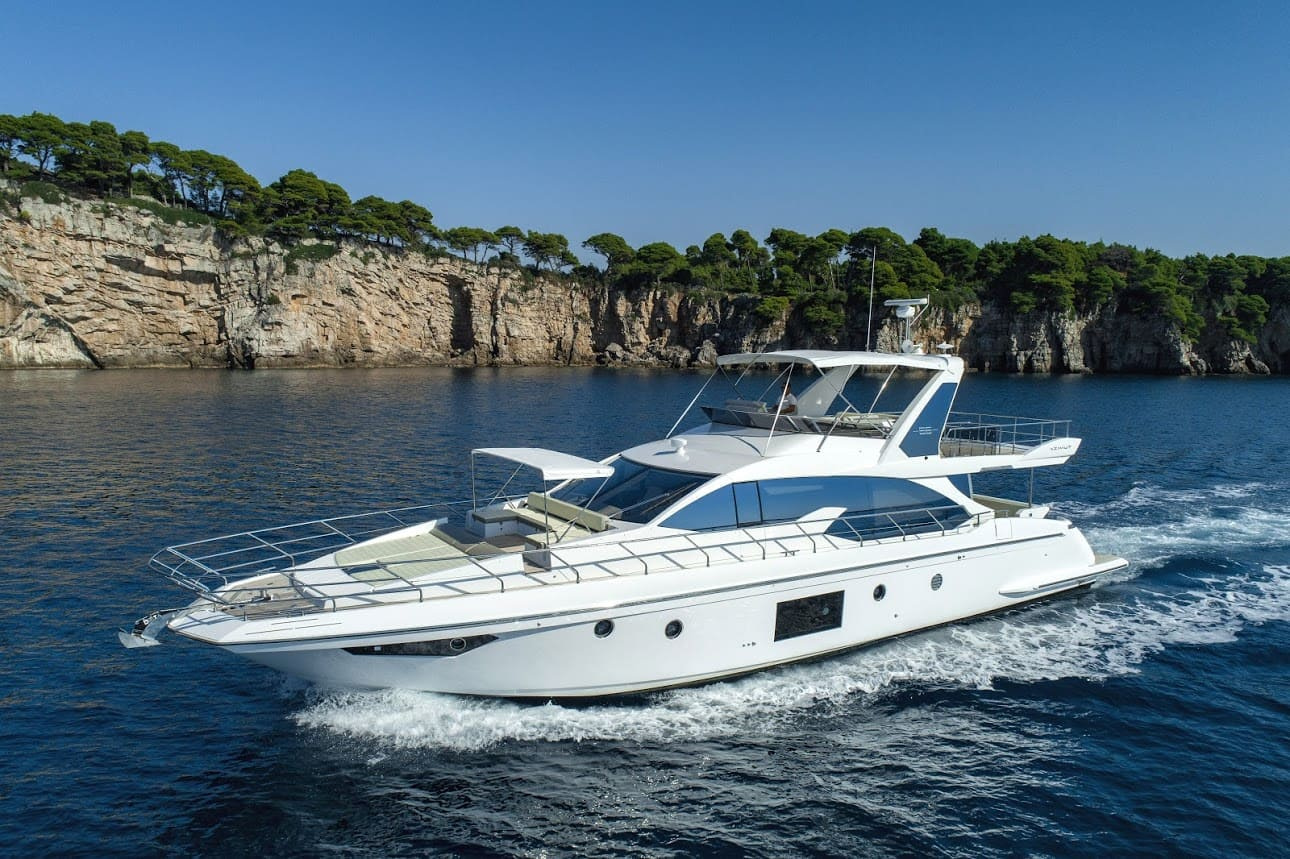 Side view of the Azimut luxury yacht cruising in front of Kolocep island