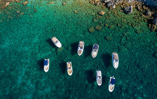 Aerial view of 8 motor boats floating in crystal clear sea nearby an island