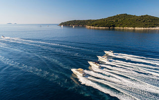 4 motor boats cruising on a sunny day nearby Lokrum island