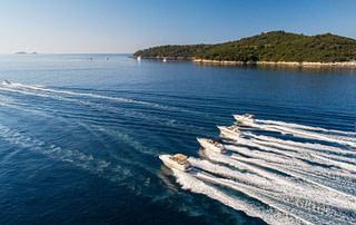 4 motor boats cruising on a sunny day nearby Lokrum island
