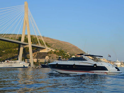 yacht for rent passing under the Dubrovnik bridge