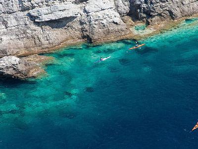 three canoes paddling close to the shore of the Shipan elaphiti island