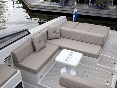 speed boat cockpit with light brown cushion and teak deck
