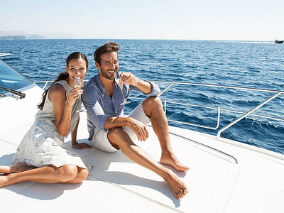 middle age couple in fine clothes are sitting on the motor boat bow and drinking white wine