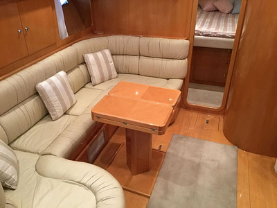 motor yacht uniesse 42 open interior with wooden table and large sofa in the corner