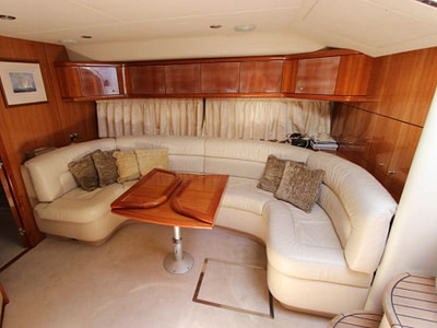 Yacht interior with large couch and wooden table