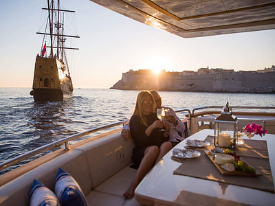couple sitting in the yacht cockpit, with a view of dubrovnik city walls