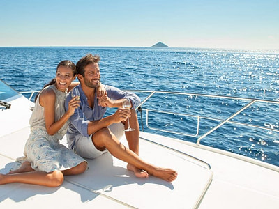 Couples enjoying champagne on a boat tour in front of Sipan island