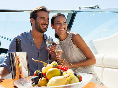 Couple travel on a motor boat with champagne and healthy snacks
