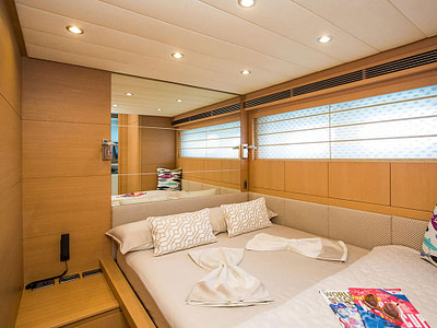 luxury yacht cabin, build with natural colour wood. newspapers and sunglasses are left on the bad sheets
