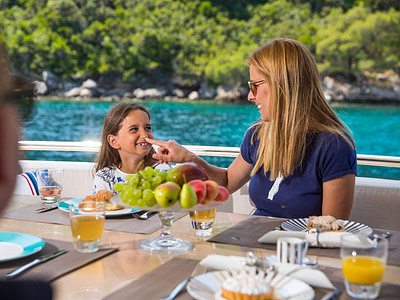 mother and daughter eating fruits in the back of the luxury yacht FILIPPETTI F76