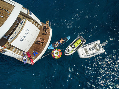 guests that rented the yacht are playing with jetski, paddle board, dinghy, wakeboard, skies and other watersport equipment on the yacht platform.