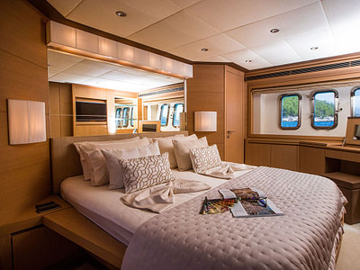 interior of luxury yacht cabin with bed full of cushions and soft mattress available for rent in dubrovnik