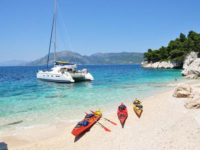 Three kayaks on a beach and a catamaran anchored nearby