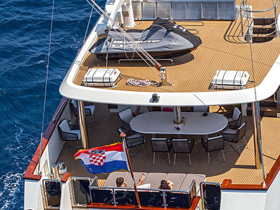 Rear view of a Navilux sailing yacht with women lounging on the bottom floor and a jet skii on the top floor