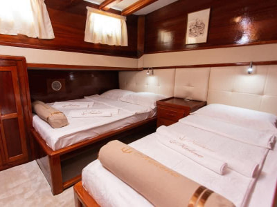 Two single beds in cabin onboard a wooden ship