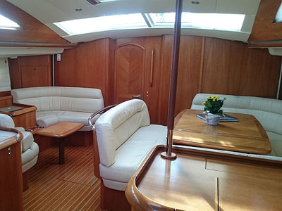 Saloon with wooden tables and leather seats inside a sailing boat
