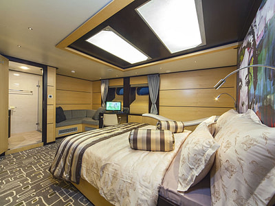 Double bed, couch and work table inside a guest cabin onboard a sailing yacht