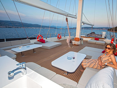 Woman lounging outside on a sailing yacht at dusk
