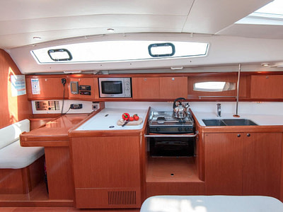 Indoor kitchen with stove, microwave and sink inside of a sailing boat