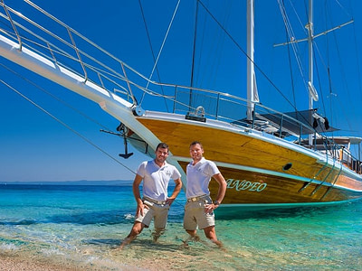 Two crew members posing in the sea in front of a large wooden ship