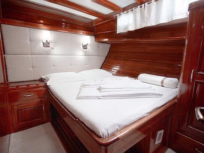 Double bed in a wooden guest cabin on a gulet