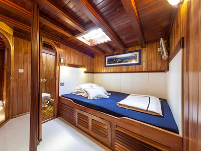 Single bed with an ensuite bathroom in a guest cabin on a ship