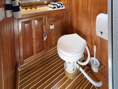 Toilet and sink with wooden interior inside a ship