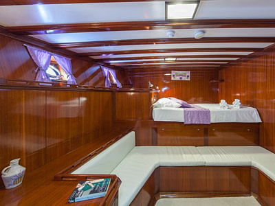 High double bed and seating area inside a wooden ship cabin