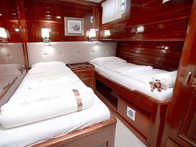 Two single beds in a guest cabin on a wooden ship