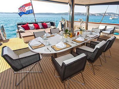 Shaded outdoor dining table and chairs with lounge area, on a yacht