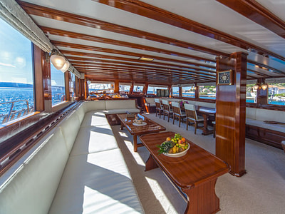 Huge indoor dining and lounge area with wooden tables and leather couches on a ship