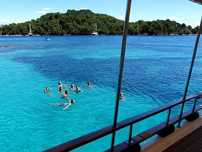 View from a ship, of a group swimming in turquoise sea next to an island