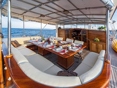Dining table set up for dinner on a wooden gulet ship at sea
