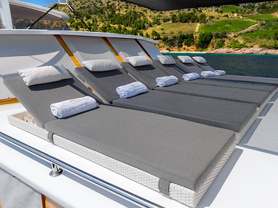 6 sun beds on the sundeck of a gulet ship next to an island
