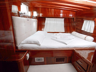 Double bed in a wooden cabin on a ship
