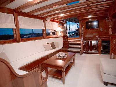 Indoor lounge area with a couch, wooden details and tv onboard a gulet