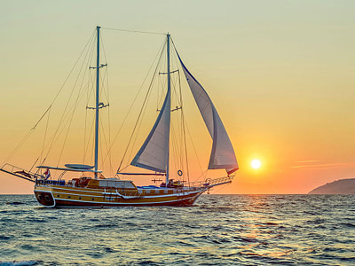 Luxurious large wooden ship sailing in front of a sunset