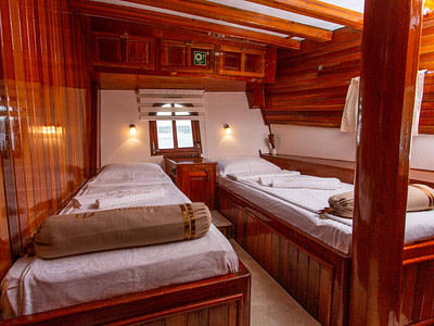 Two single beds in a beautiful wooden cabin board a large gulet