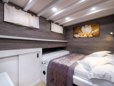 Luxurious wooden cabin with a double bed onboard a gulet