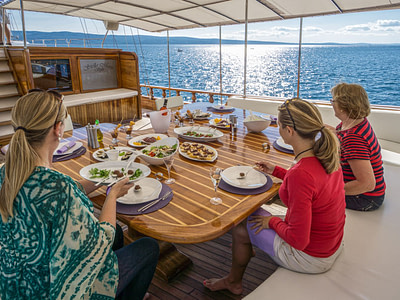 Three guests eating a meal outdoor on a wooden ship with a view of the sea and islands