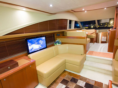 Modern saloon with TV and leather sofas onboard motor yacht