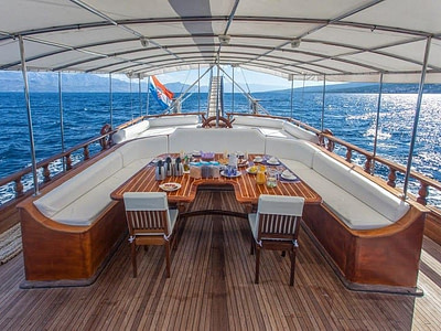 Large shaded outdoor dining table and sofa chairs onboard a ship