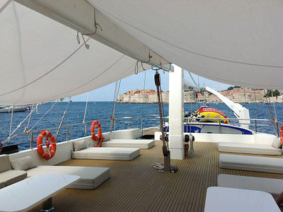 Outdoor shaded are with sun beds onboard a sailing yacht in front of Dubrovnik Croatia