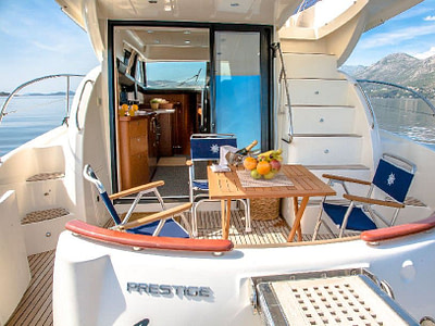 Main deck of a Prestige 440 yacht with an outdoor table, chairs, fruit bowl and champagne
