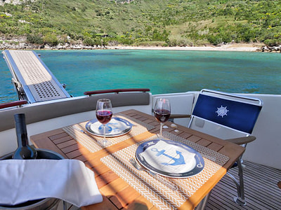 Table set up for dining, on on the main deck of a yacht nearby an island