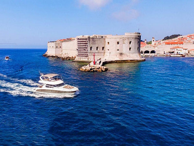 Prestige 440 yacht cruising the sea on a sunny day in front of the Old Town of Dubrovnik, Croatia
