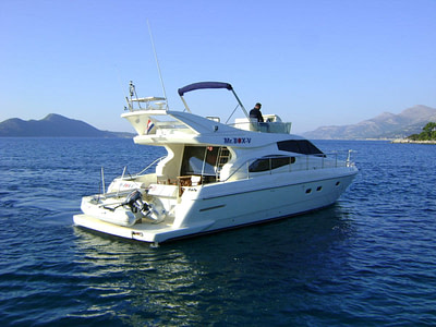 Captain on a roof deck of a Ferretti 480 yacht nearby islands