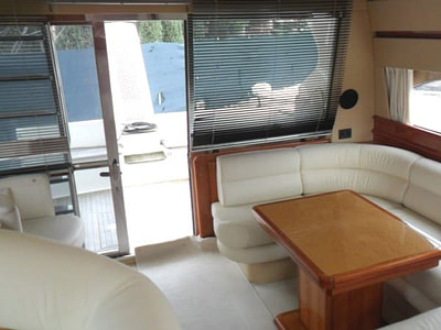 Leather couch and wooden table in a saloon onboard a Ferretti 480 yacht